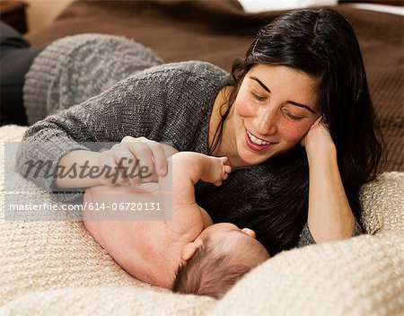 Mother cradling newborn infant on bed Stock Photo - Premium Royalty-Free, Image code: 614-06720131