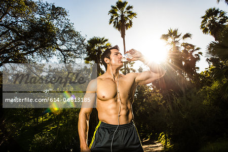 Young man exercising in forest drinking mineral water Stock Photo - Premium Royalty-Free, Image code: 614-06813185