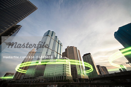 Green light trails surrounding skyscrapers Stock Photo - Premium Royalty-Free, Image code: 614-06813408