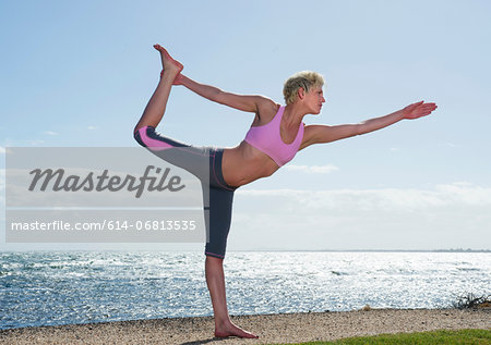 Young woman doing yoga by sea Stock Photo - Premium Royalty-Free, Image code: 614-06813535