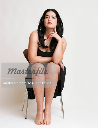 Young woman sitting on chair Stock Photo - Premium Royalty-Free, Image code: 614-06813583