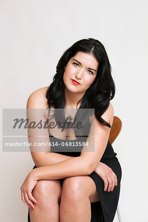 Young woman sitting on chair Stock Photo - Premium Royalty-Free, Image code: 614-06813584