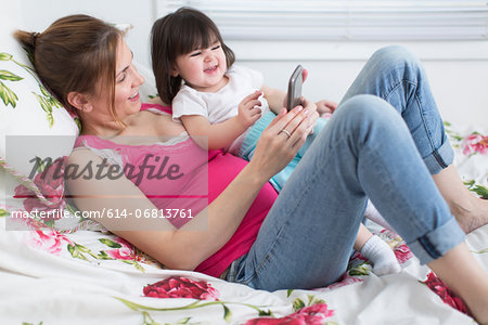 Portrait of pregnant woman and toddler daughter lounging on bed playing with smartphone Stock Photo - Premium Royalty-Free, Image code: 614-06813761