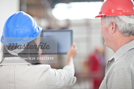 Back view of co-workers looking at digital tablet on construction site Stock Photo - Premium Royalty-Free, Image code: 614-06813839