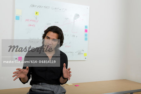Young man with whiteboard in background Stock Photo - Premium Royalty-Free, Image code: 614-06814119