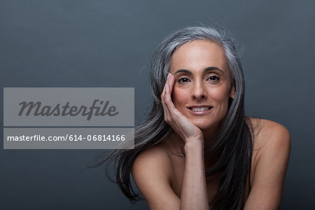 Mature woman with hand on chin Stock Photo - Premium Royalty-Free, Image code: 614-06814166