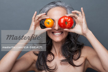 Mature woman covering eyes with red and yellow tomato Stock Photo - Premium Royalty-Free, Image code: 614-06814171