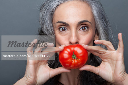Mature woman covering mouth with red tomato Stock Photo - Premium Royalty-Free, Image code: 614-06814172