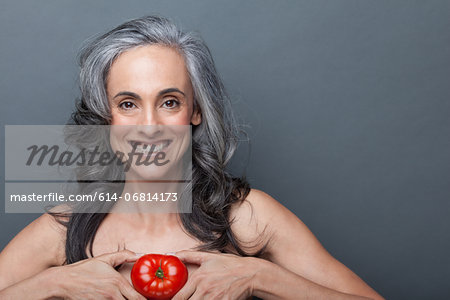 Mature woman holding red tomato Stock Photo - Premium Royalty-Free, Image code: 614-06814173