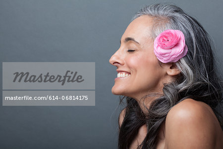 Mature woman with pink flower in hair, eyes closed Stock Photo - Premium Royalty-Free, Image code: 614-06814175