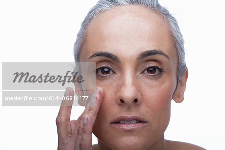 Mature woman touching face Stock Photo - Premium Royalty-Free, Image code: 614-06814177