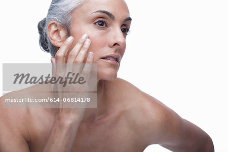 Mature woman touching face Stock Photo - Premium Royalty-Free, Image code: 614-06814178