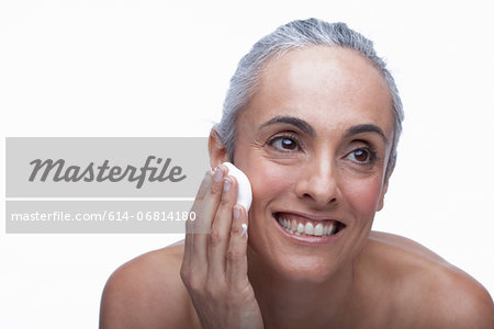 Mature woman cleansing face Stock Photo - Premium Royalty-Free, Image code: 614-06814180