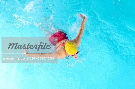Mature woman doing butterfly stroke in swimming pool Stock Photo - Premium Royalty-Free, Image code: 614-06814263