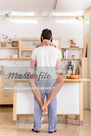 Young couple embracing in kitchen Stock Photo - Premium Royalty-Free, Image code: 614-06814317