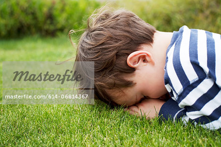 Male toddler hiding face down on grass Stock Photo - Premium Royalty-Free, Image code: 614-06814367