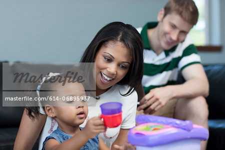 Mid adult woman watching daughter play with toys, smiling