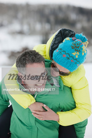 Mature man carrying young woman on back in snow, laughing Stock Photo - Premium Royalty-Free, Image code: 614-06896077