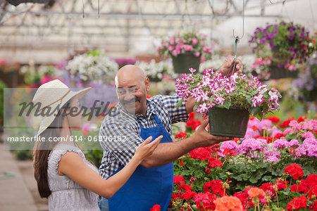 Mature man serving young woman in garden centre, smiling Stock Photo - Premium Royalty-Free, Image code: 614-06896182