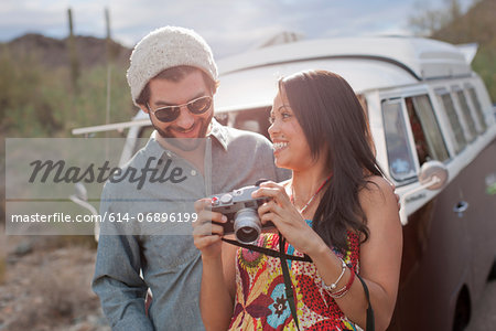 Young woman holding camera with boyfriend on road trip, smiling Stock Photo - Premium Royalty-Free, Image code: 614-06896199
