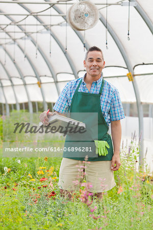 Mature man holding clipboard in garden centre, portrait Stock Photo - Premium Royalty-Free, Image code: 614-06896281