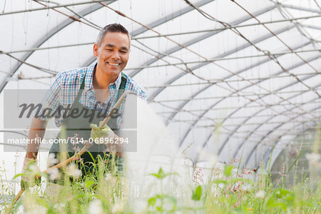 Mature man watering plants in garden centre Stock Photo - Premium Royalty-Free, Image code: 614-06896294