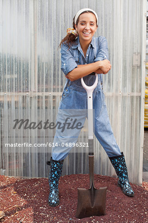 Young woman in dungarees leaning on spade in garden centre, portrait Stock Photo - Premium Royalty-Free, Image code: 614-06896321
