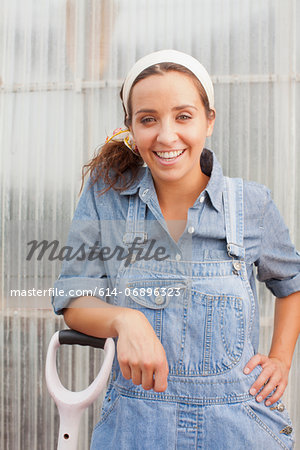 Young woman in dungarees leaning on spade in garden centre, portrait Stock Photo - Premium Royalty-Free, Image code: 614-06896323