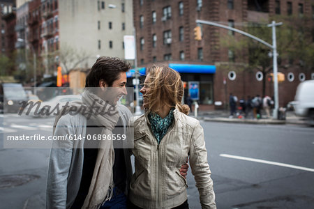 Smiling couple walking together down city street Stock Photo - Premium Royalty-Free, Image code: 614-06896559