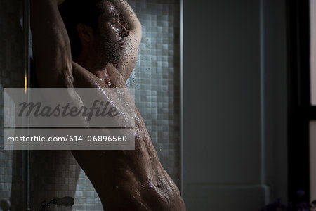 Mid adult male taking a shower Stock Photo - Premium Royalty-Free, Image code: 614-06896560