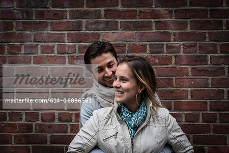 Portrait of smiling couple in front of brick wall Stock Photo - Premium Royalty-Free, Image code: 614-06896561