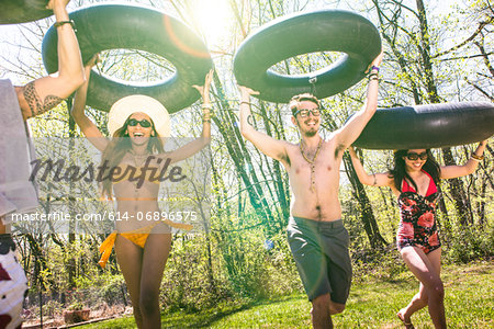 People carrying inner tubes above heads, laughing Stock Photo - Premium Royalty-Free, Image code: 614-06896575