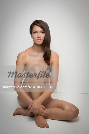 Portrait of naked woman sitting on floor Stock Photo - Premium Royalty-Free, Image code: 614-06896619