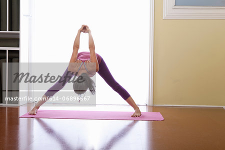 Woman bending forwards with arms raised Stock Photo - Premium Royalty-Free, Image code: 614-06896667