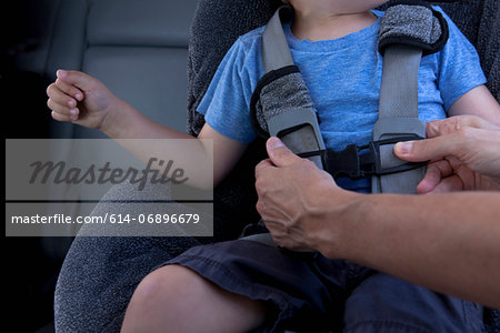 Mother fastening child safety seat belt in car Stock Photo - Premium Royalty-Free, Image code: 614-06896679