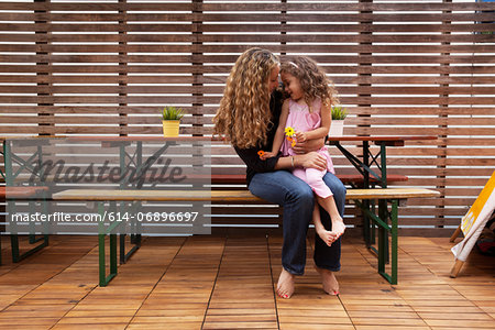 Mother and daughter sitting on bench on patio Stock Photo - Premium Royalty-Free, Image code: 614-06896697