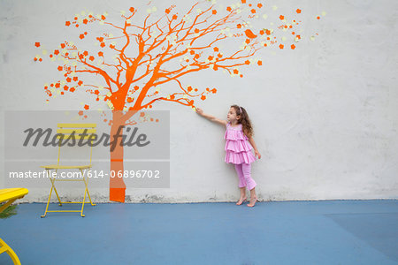 Girl pointing to orange tree mural on wall Stock Photo - Premium Royalty-Free, Image code: 614-06896702