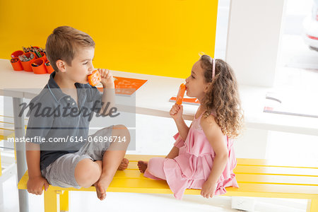 Brother and sister eating ice lollies on bench indoors Stock Photo - Premium Royalty-Free, Image code: 614-06896714