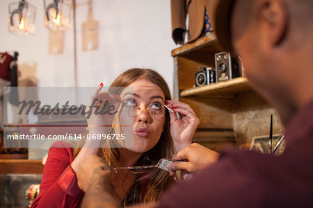 Woman in vintage shop trying on glasses and pulling faces Stock Photo - Premium Royalty-Free, Image code: 614-06896725