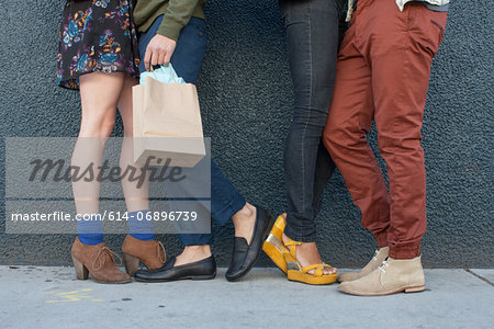 Four young adults standing by wall, low section Stock Photo - Premium Royalty-Free, Image code: 614-06896739