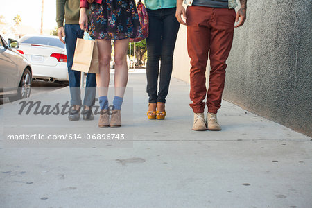 Four young adults standing on pavement, low section Stock Photo - Premium Royalty-Free, Image code: 614-06896743