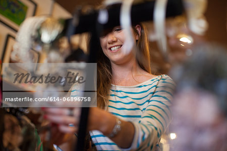 Young woman looking through clothes rail in vintage shop Stock Photo - Premium Royalty-Free, Image code: 614-06896758
