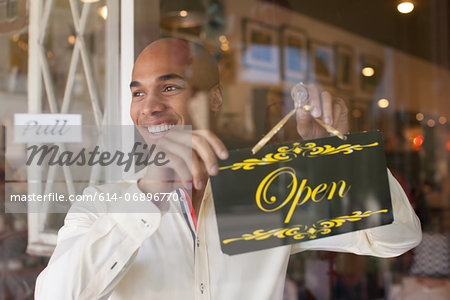 Shopkeeper turning open sign on vintage shop door Stock Photo - Premium Royalty-Free, Image code: 614-06896770