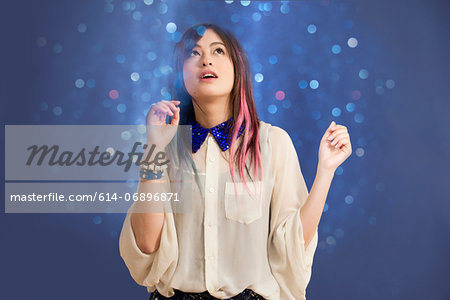 Portrait of young woman looking up at glitter Stock Photo - Premium Royalty-Free, Image code: 614-06896871