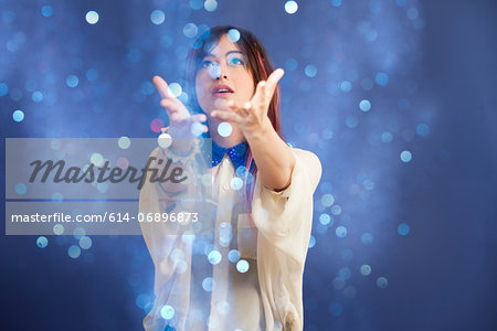 Portrait of young woman catching glitter Stock Photo - Premium Royalty-Free, Image code: 614-06896873