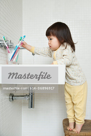 Girl toddler on tiptoe reaching over bathroom sink Stock Photo - Premium Royalty-Free, Image code: 614-06896917
