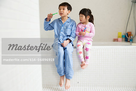 Brother and sister sitting on edge of bath with toothbrushes Stock Photo - Premium Royalty-Free, Image code: 614-06896919
