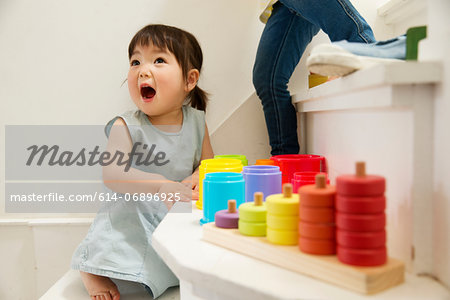 Female toddler playing with toys on staircase Stock Photo - Premium Royalty-Free, Image code: 614-06896925