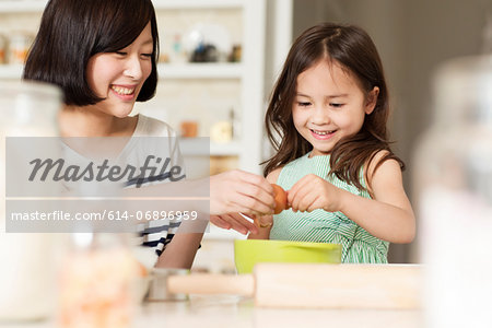 Mother and young daughter cracking egg into mixing bowl Stock Photo - Premium Royalty-Free, Image code: 614-06896959