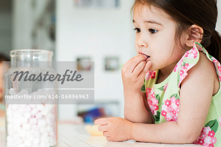 Close up of young girl tasting marshmallows Stock Photo - Premium Royalty-Free, Image code: 614-06896963